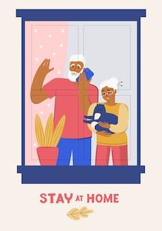 Ouderen worden thuis in quarantaine geplaatst. blijf thuis. een oudere man en vrouw kijken uit het raam naar de straat. senioren brengen samen tijd door.