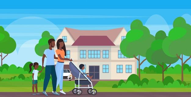 Ouders met dochter en peuter zoon in wandelwagen lopen buiten familie ouderschap concept moderne villa huis landschap achtergrond volledige lengte horizontaal