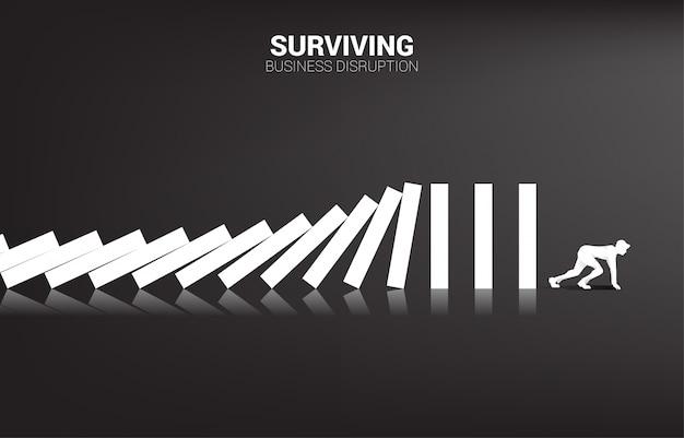 Overleven van bedrijfsverstoring. silhouet van zakenman klaar om vanaf dominoinstorting te lopen. bedrijfsleven verstoren