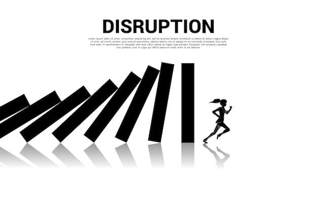 Overleven van bedrijfsverstoring. silhouet van zakenvrouw wegrennen van domino-instorting met grafiekachtergrond. concept van het bedrijfsleven verstoren