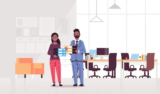 Overwerkt man vrouw bedrijf map stapel paar collega's permanent samen papierwerk hard werken concept modern kantoor interieur volledige lengte horizontaal
