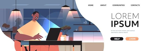 Overwerkte zakenman freelancer kijken naar laptop scherm man zit op werkplek in donkere nacht thuis kamer horizontale portret kopieer ruimte