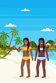 Paar bikini vrouwen op tropisch eiland met villa bungalow hotel op strand aan zee groene palmen landschap zomervakantie plat
