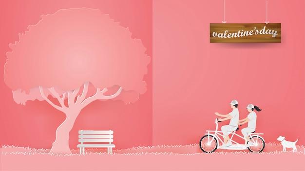 Paar dat een fiets op het rode gras op roze achtergrond berijdt