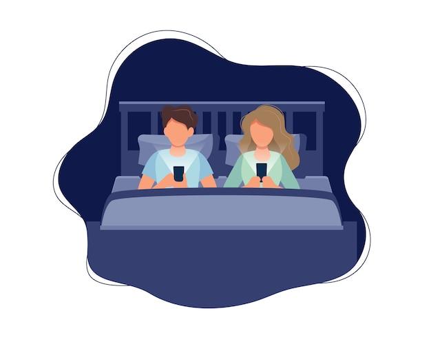 Paar dat in bed met telefoons legt bij nacht.