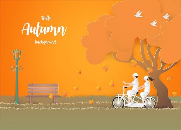 Paar die door fiets op het gras op de herfstachtergrond reizen.