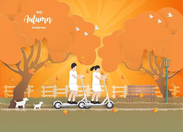 Paar die een elektrische autoped op de herfstachtergrond berijden.