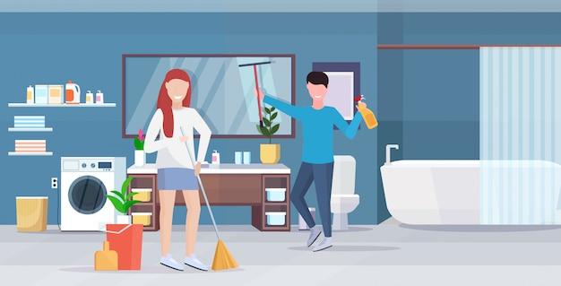 Paar doen huishoudelijk werk samen man veegglas spiegel vrouw vegen vloer met bezem schoonmaak concept moderne badkamer interieur volledige lengte horizontaal