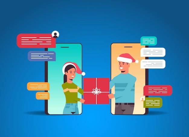 Paar in santa hoeden met behulp van chatten app sociaal netwerk chat bubble communicatieconcept