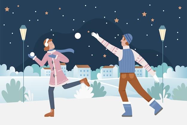 Paar mensen spelen 's nachts sneeuwballen op kerstavond