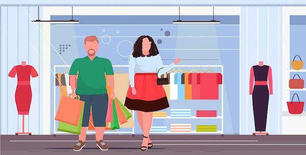 Paar met kleurrijke papieren zakken overgewicht man vrouw met aankopen winkelen concept moderne mode winkel vrouwelijke kleding boetiek interieur plat volledige lengte horizontaal