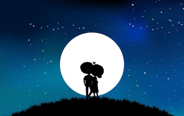 Paar op de top van de berg silhouet tegen de maan