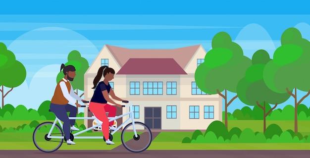 Paar rijden tandem fiets afro-amerikaanse man met overgewicht man fietsen twin fiets samen training gewichtsverlies concept villa huis landschap achtergrond volledige lengte