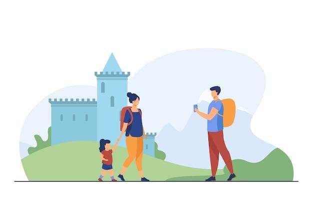 Paar toeristen met kind bij oriëntatiepunt. mensen met rugzakken fotograferen bij kasteel platte vectorillustratie. vakantie, gezinsreisconcept