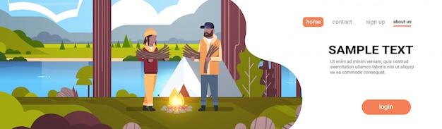 Paar toeristen wandelaars houden brandhout man vrouw brand organiseren in de buurt van kamp tent wandelen camping concept landschap natuur rivier bergen achtergrond horizontale volledige lengte kopie ruimte
