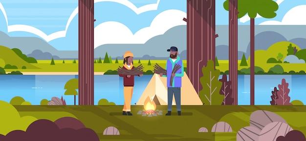 Paar toeristen wandelaars houden brandhout man vrouw het organiseren van brand in de buurt van kamp tent wandelen camping concept landschap natuur rivier bergen achtergrond horizontale volledige lengte