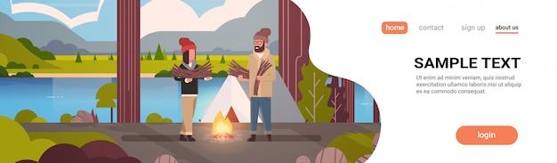 Paar toeristen wandelaars houden brandhout man vrouw het organiseren van brand in de buurt van kamp tent wandelen camping concept landschap natuur rivier bergen