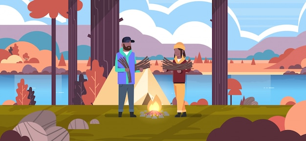 Paar toeristen wandelaars houden brandhout man vrouw organiseren brand n kamp tent wandelen camping concept herfst landschap natuur rivier bergen achtergrond horizontale volledige lengte