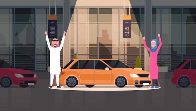 Paar van arabische verkoper presenteren nieuwe auto in dealercentrum showroom over set van nieuwe voertuigen horizontale afbeelding