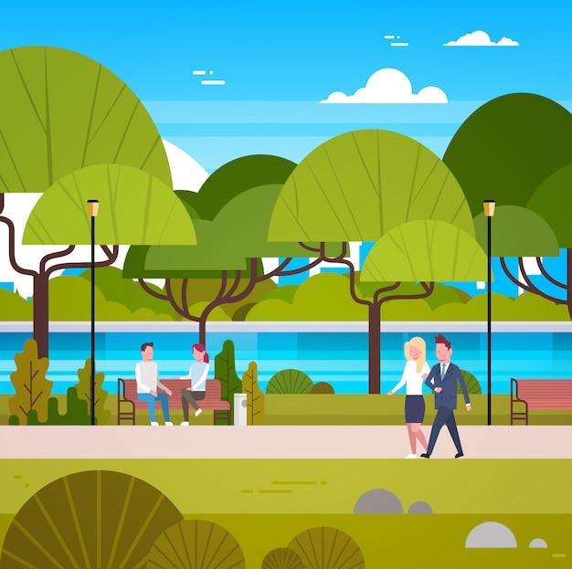 Paar van bedrijfsmensen die in mooi stedelijk park lopen die in openlucht ontspannen