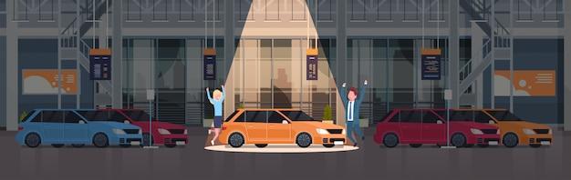 Paar van verkoper presenteren nieuwe auto in dealercentrum showroom over set van nieuwe voertuigen horizontale afbeelding