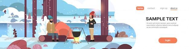 Paar wandelaars man vrouw koken maaltijden in bowler kookpot bij kampvuur in de buurt van kamp tent camping concept winterlandschap natuur rivier bergen sneeuwval