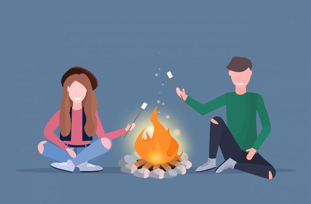 Paar wandelaars roosteren marshmallow snoep op kampvuur wandelen camping concept man vrouw reizigers op wandeling horizontale volledige lengte plat