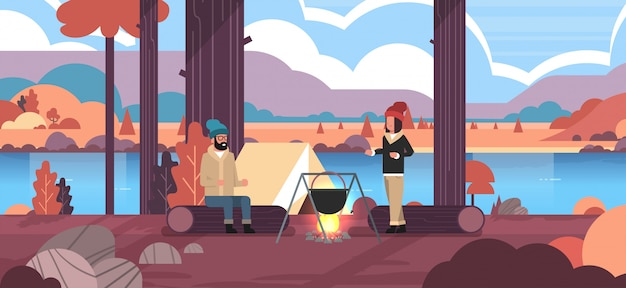 Paar wandelaars zittend op log man vrouw koken maaltijden in bowler kookpot bij kampvuur in de buurt van kamp tent camping concept herfst landschap natuur rivier bergen