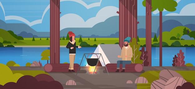 Paar wandelaars zittend op log man vrouw koken maaltijden in bowler kookpot bij kampvuur in de buurt van kamp tent kamperen landschap natuur rivier bergen