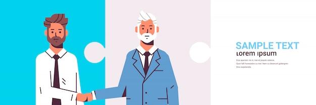 Paar zakenlieden handshaking zakenpartners handbewegingen tijdens vergadering overeenkomst partnerschap concept mannelijke collega's permanent samen vlak portret horizontale puzzelstukjes kopie ruimte