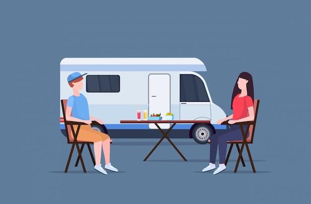 Paar zittend aan tafel in de buurt van camping familie aanhangwagen vrachtwagen caravan auto man vrouw tijd doorbrengen zomervakantie concept platte volledige lengte horizontaal