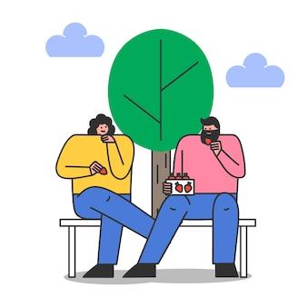 Paar zittend op een bankje in het park en aardbei eten. jonge man en vrouw op date buitenshuis