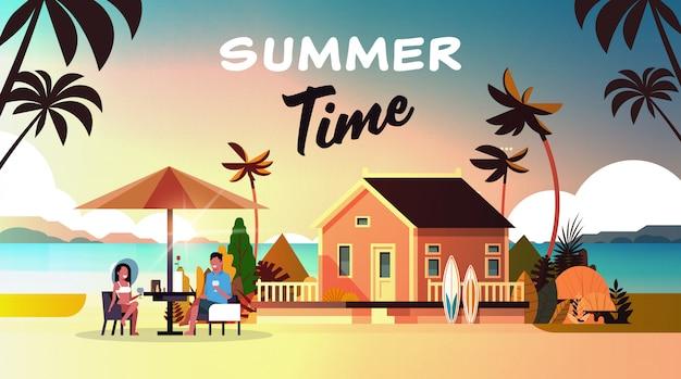 Paar zomervakantie man vrouw drinkt wijn paraplu op zonsondergang strand villa huis tropisch eiland