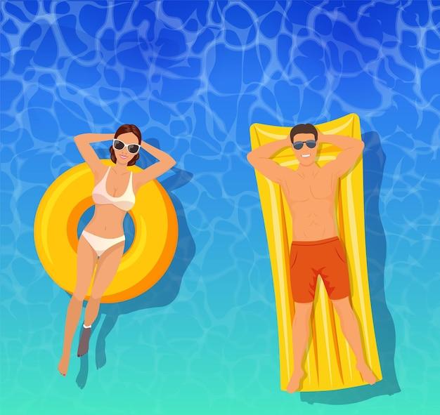 Paar zonnebaden bovenaanzicht. man en vrouw zwemmen op opblaasbare drijvers.