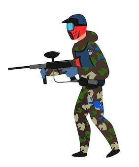 Paintball speler in staande positie geïsoleerd op wit man in vuile militaire camouflage en beschermend blauw masker schieten pistool in handen houden