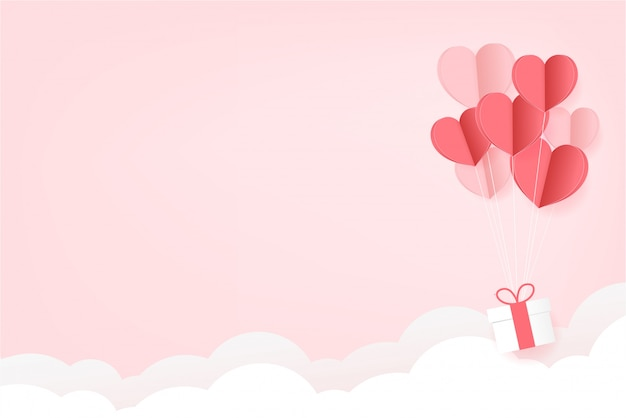 Paper hearts float op roze achtergrond. valentijnsdag