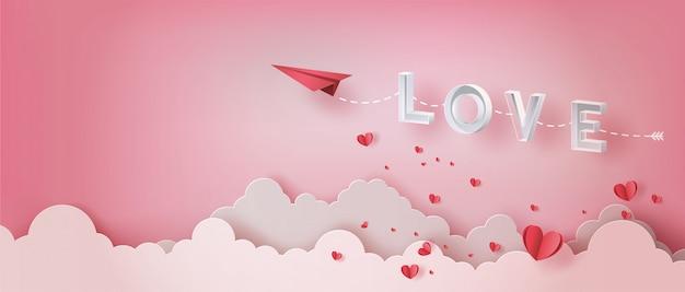 Papier vliegtuig vliegt in de lucht met letter liefde en vele harten zweven.