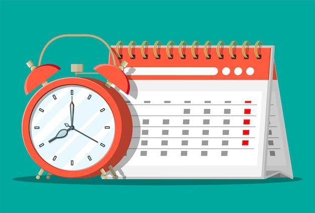 Papieren spiraalwandkalender en klokken. kalender en wekkers. schema, afspraak, organisator, urenstaat, tijdbeheer, belangrijke datum.
