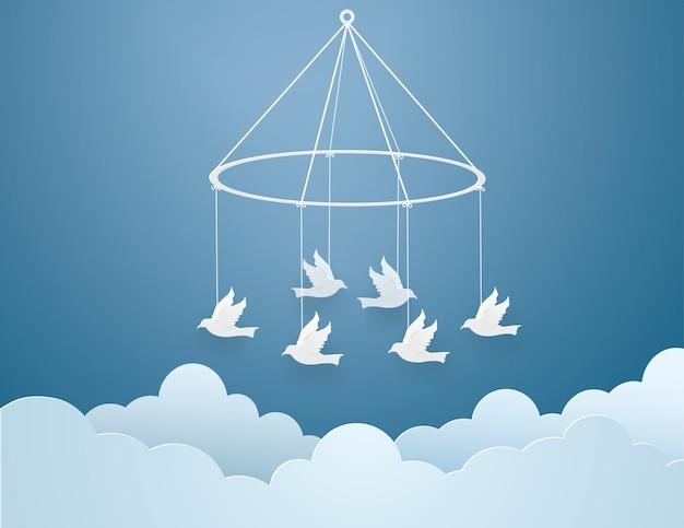 Papieren vogels gebonden met wit touw aan de hemel