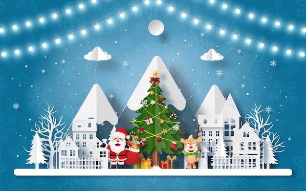 Papierkunst van de kerstman en rendieren in het dorp bij de sneeuwberg