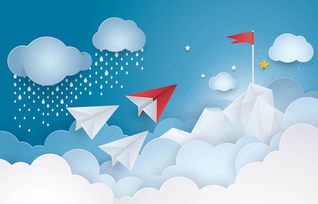 Papiervliegtuig die aan de rode vlagbovenkant vliegen van een berg in hemelwolk
