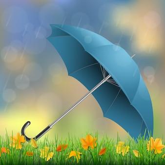 Paraplu liggend op het gras met gevallen bladeren in de regen.