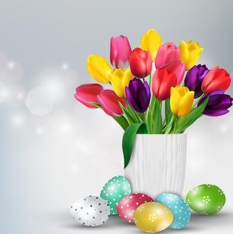Pasen-achtergrond met kleurrijke eieren en tulpen in witte vas