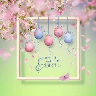 Pasen decoratief frame met bloeiende lentetakken, hangende beschilderde eieren en vallende bloemblaadjes