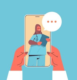 Patiënt bespreken met arabische vrouwelijke arts in smartphonescherm chat bubble communicatie online overleg gezondheidszorg geneeskunde medisch advies concept