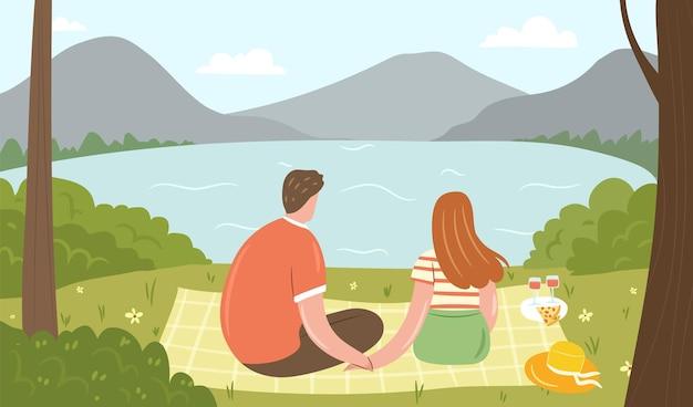 Picknick in het bos gelukkig paar op een deken tussen bomen kijkend naar de bergen en het meerlandschap