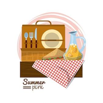 Picknickmand op tafelkleed met sandwich en sappot