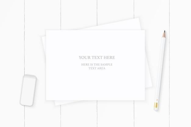 Plat lag bovenaanzicht elegante witte compositie papier potlood en gum op houten achtergrond.