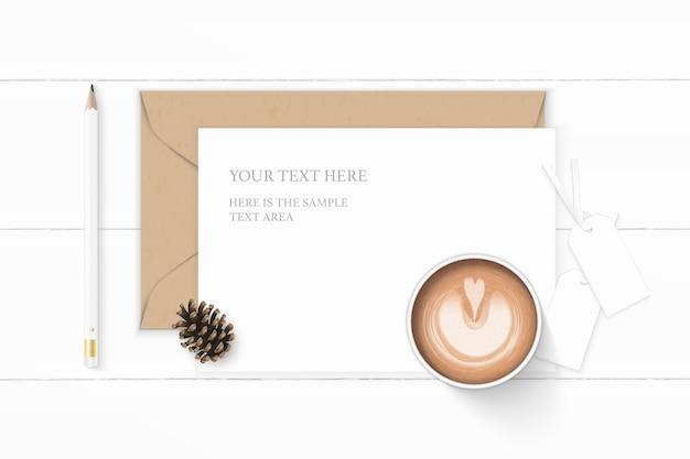Plat lag bovenaanzicht elegante witte samenstelling brief kraftpapier envelop dennenappel en potlood koffie op houten achtergrond.