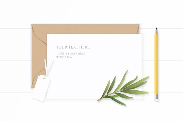 Plat lag bovenaanzicht elegante witte samenstelling brief kraftpapier envelop geel potlood dragon blad en label op houten achtergrond.
